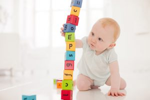 Baby on floor pulling wood block from middle of stack